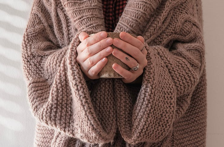A woman in an oversized brown knit sweater stands with her hands on a hot drink.