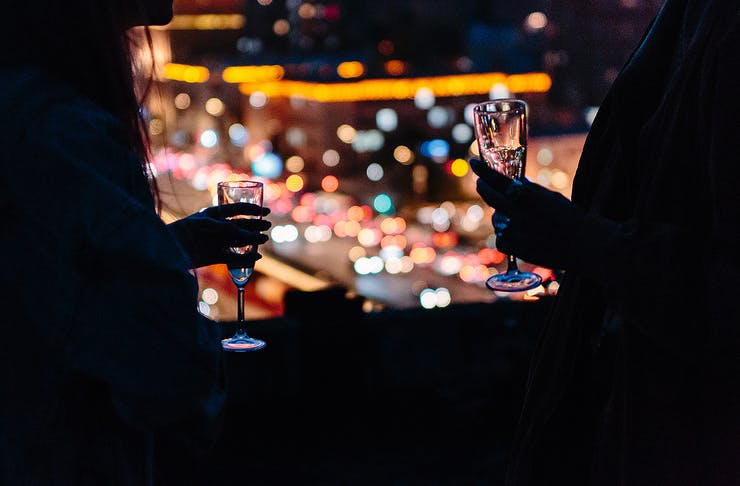 A couple holding champagne flutes in a darkened bar.
