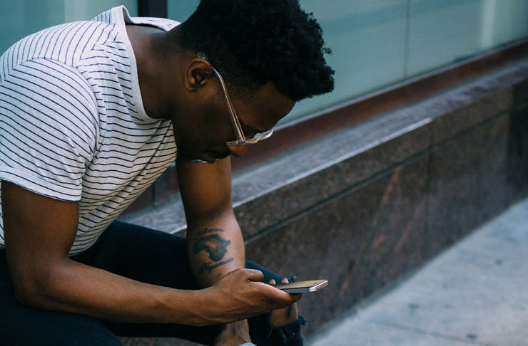 Man sitting on the edge of a wall, looking intently at his phone