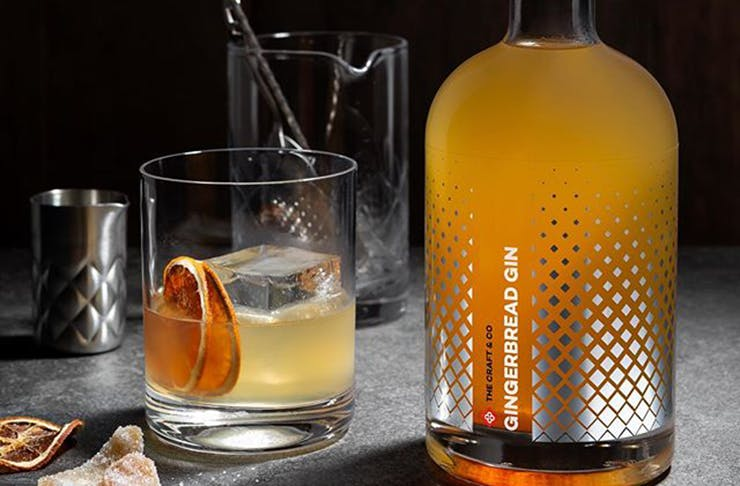 A bottle of orange coloured gingerbread gin next to a glass with citrus slices inside it.