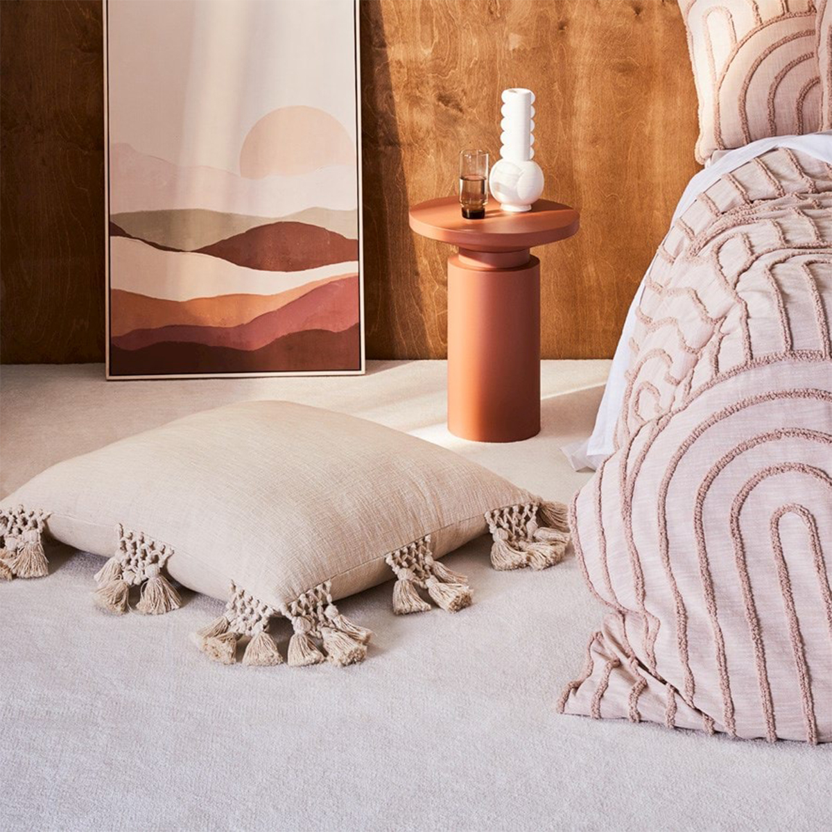 a bed, bedside table and a painting all in shades of dusty pink