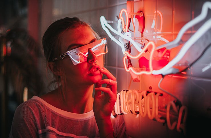 A woman in sunglasses looking at neon lights.