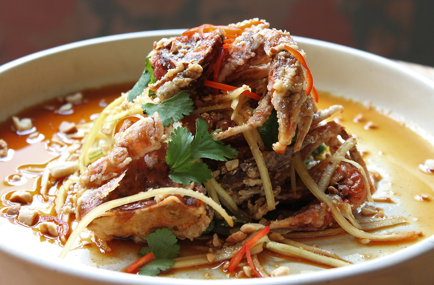 Soft Shell Crab with shredded Kohlrabi sits on a plate looking delicious.