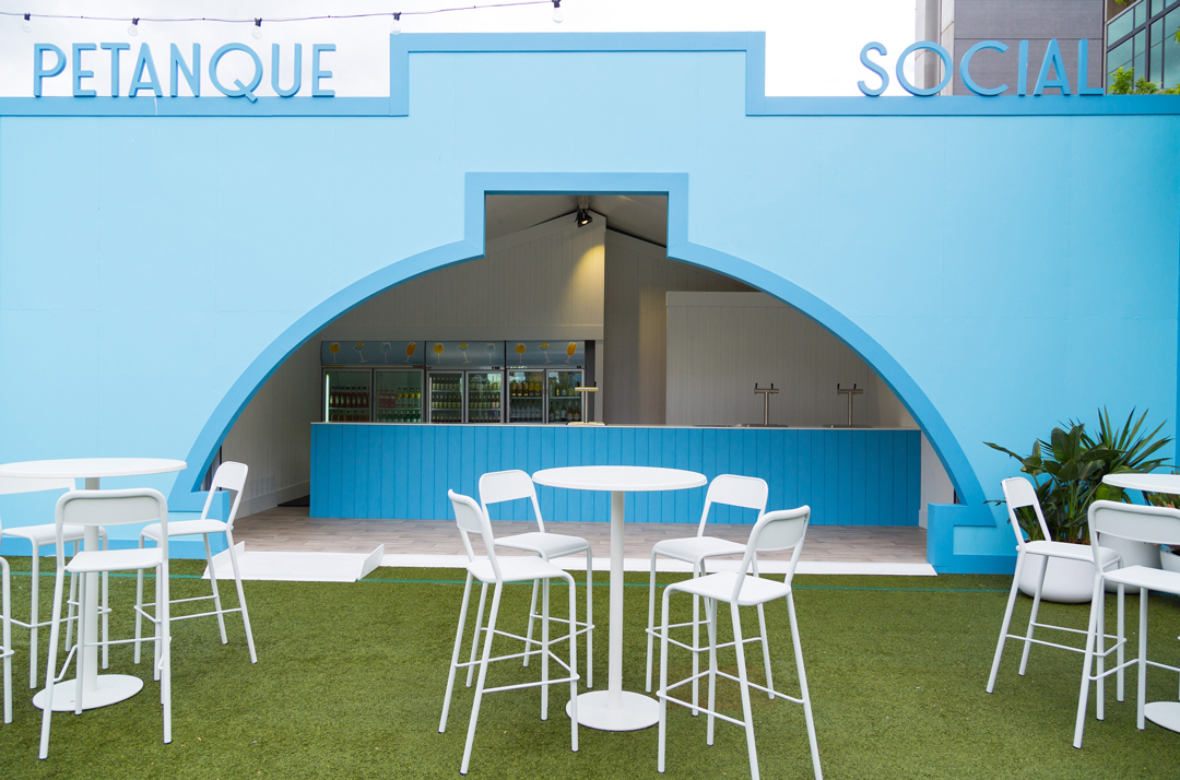Outdoor seating on green astroturf with a blue bar in the background. A large blue sign reads Petanque Social above the bar.