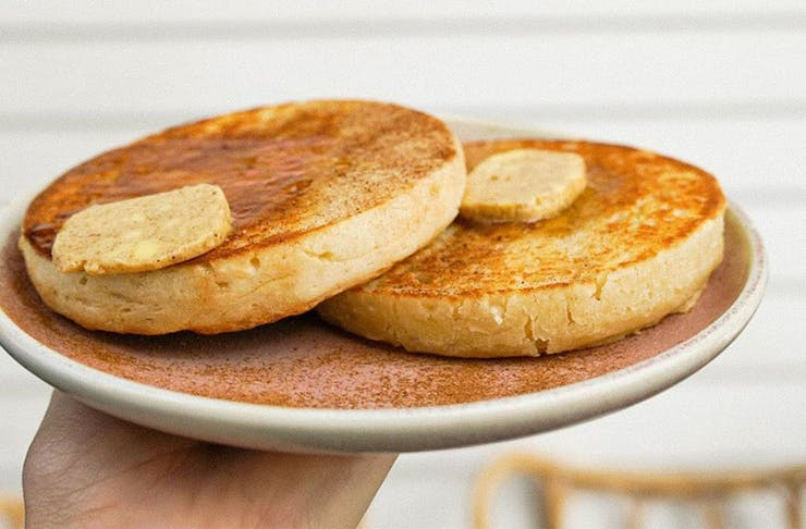 Two toasted crumpets on a plate, with melted butter dripping off the top
