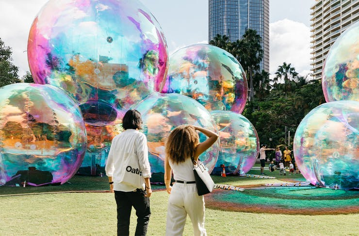 two people in front of giant bubble like structures