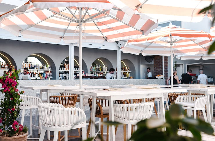 An image of a rooftop bar with high tables and striped umbrellas.