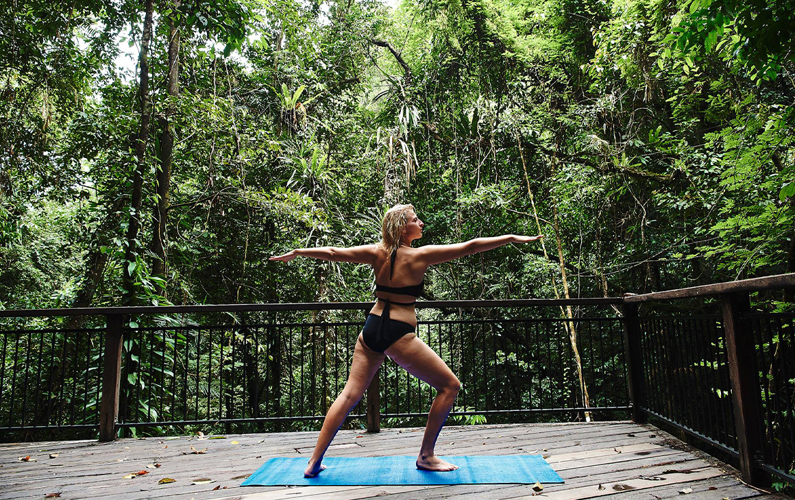 a woman doing yoga in the rainforest