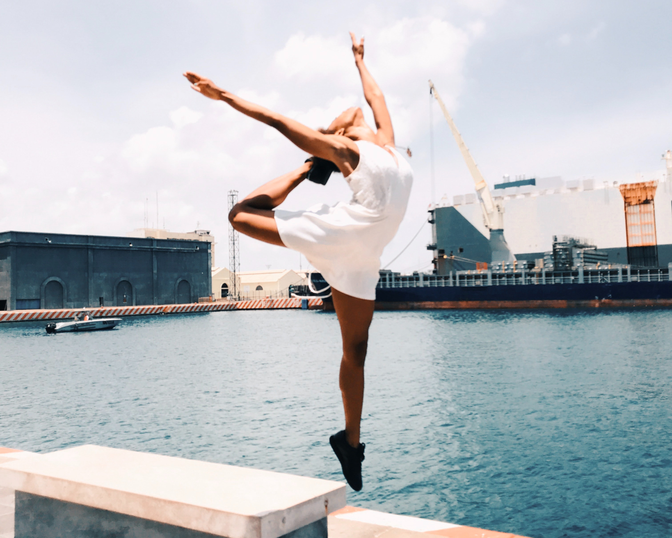 Woman jumping in mid-air with arms high, next to a city port