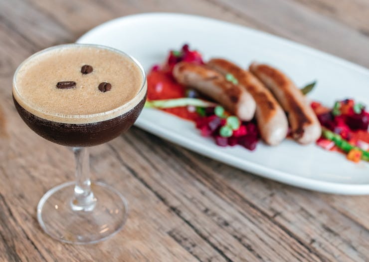 an espresso martini in front of a plate of sausages