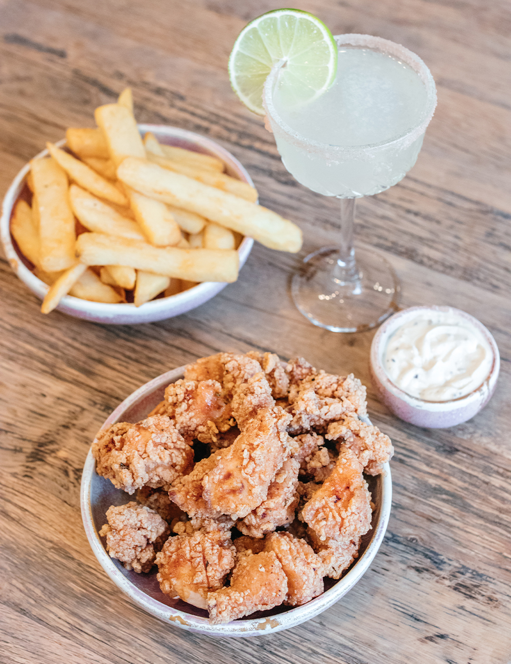 bowls of popcorn chicken and fries and a margarita