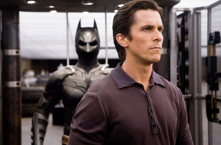 Christian Bale as Bruce Wayne, standing with his back turned to his Batsuit.