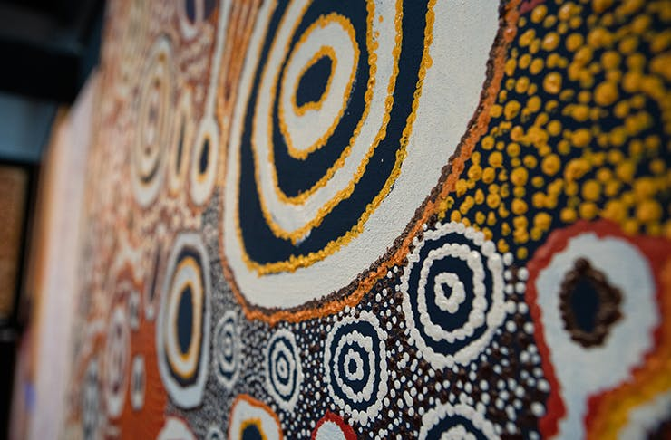 A traditional Aboriginal dot painting consisting of a large circle in the middle, which is surrounded by smaller, similar shapes.