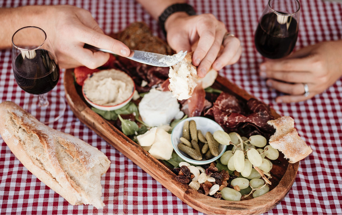 a charcuterie platter on a picnic blanket with wine