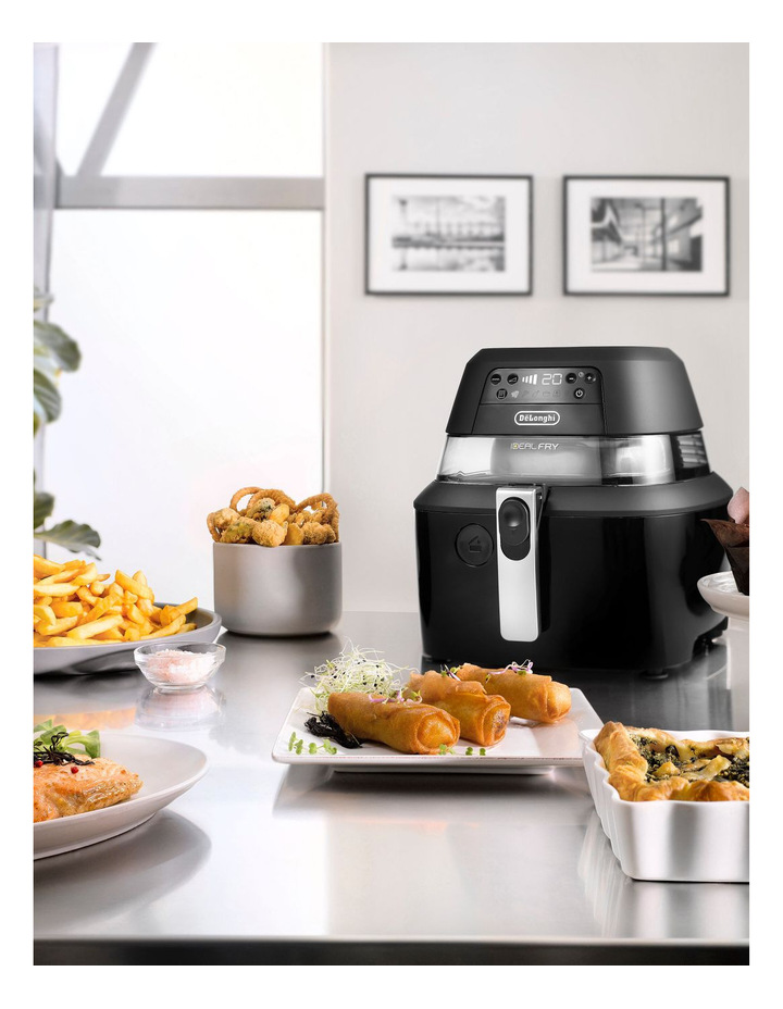 An air fryer on a kitchen table next to a stack of food.