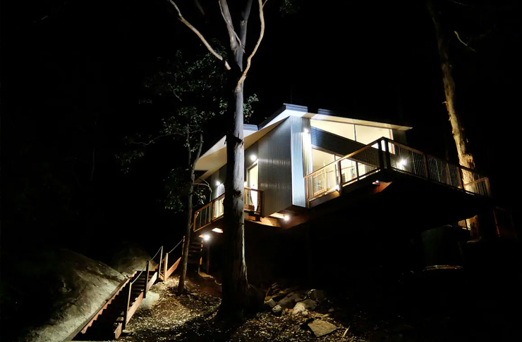 A treehouse between two gumtrees lit up at night.