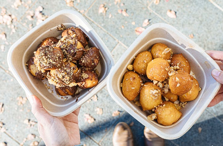 two takeaway boxes of loukoumades, one with nutella and one with honey and nuts
