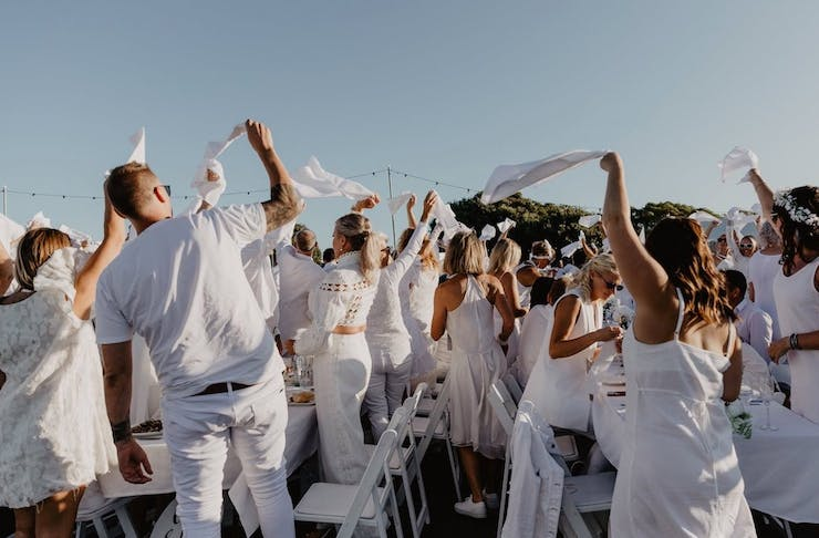 Diner En Blanc guests all dressed in white waving white cloths