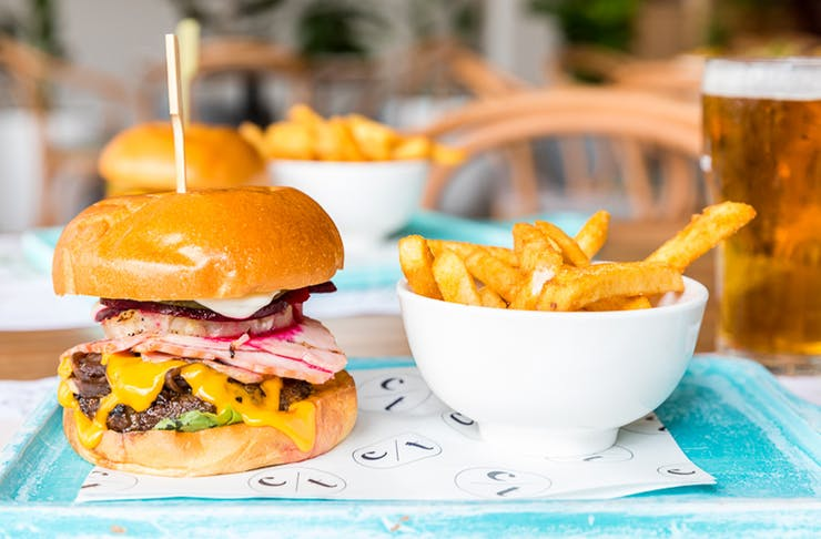 a burger and a bowl of chips on a tray with a pint of beer
