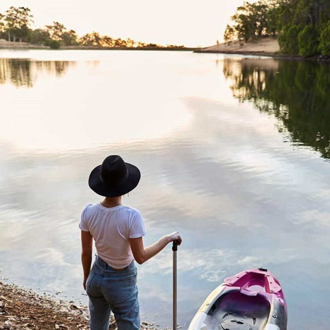 Woman stands next to a kayak at the edge of a lake in Ferguson Valley