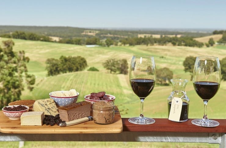 Things to do Ferguson Valley - two glasses of wine and a cheese board rest on balcony overlooking rolling green hills
