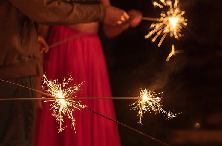 A couple hold sparklers aloft for Diwali