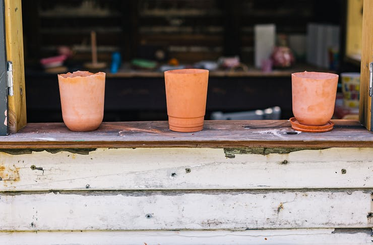 Three small terracotta pots lined up on a window sill.