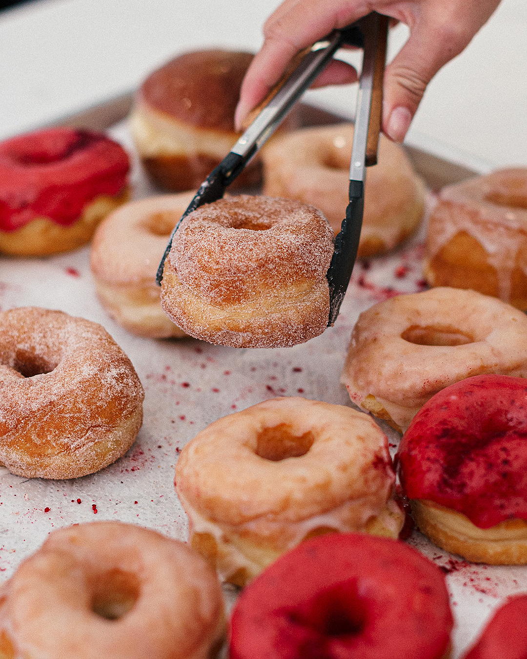 Someone picks up a deliciously sugary doughnut from doe donuts.