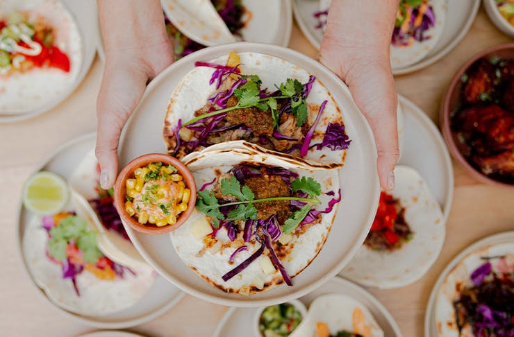 a plate of tacos being held above other plates of tacos