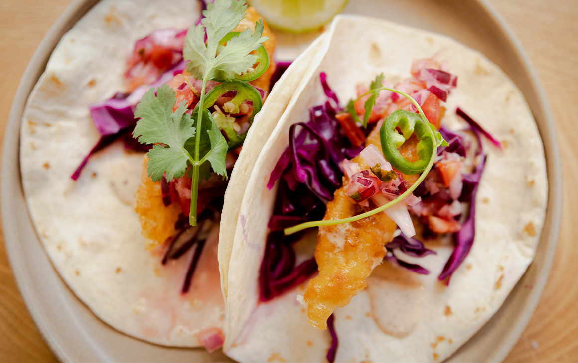 a plate of two fish tacos