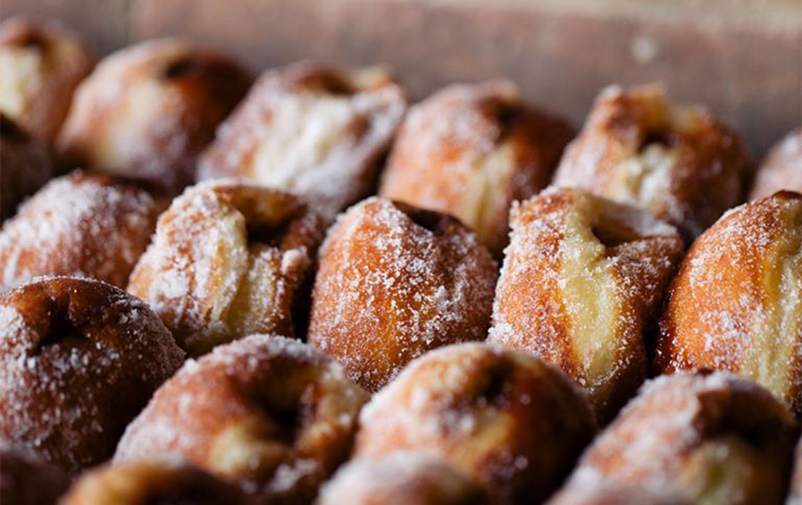 Several rows of filled, sugary doughnuts