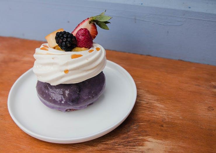 a purple iced doughnut topped with pavlova on a plate