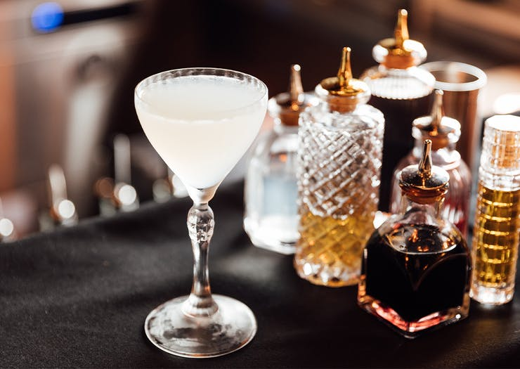 a gimlette cocktail next to small glass bottles