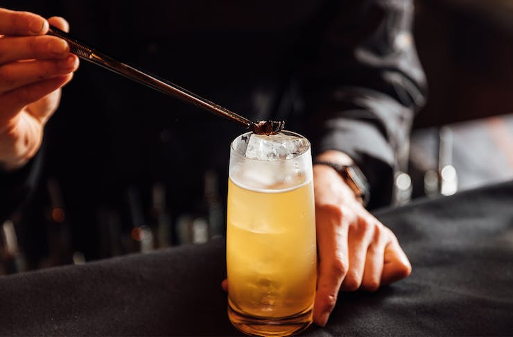 garnish being placed on top of a highball cocktail