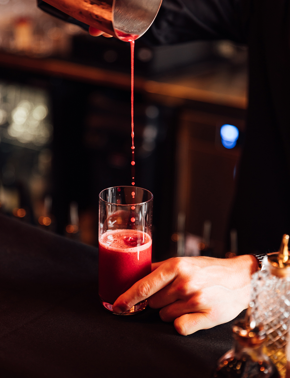 a red cocktail being poured