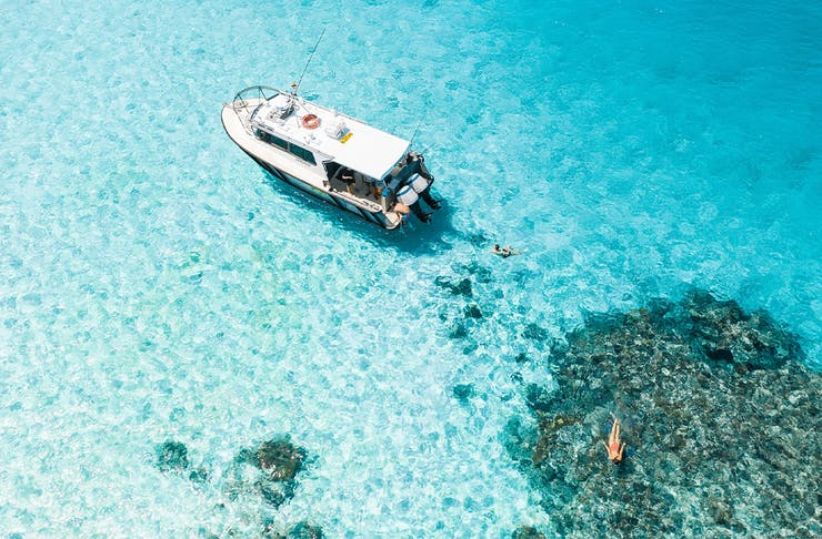 boat floating in crystal clear ocean over a reef