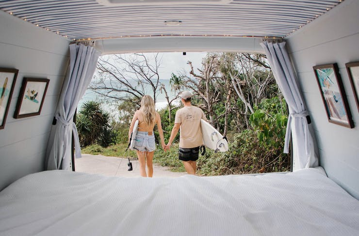 A photo taken from inside a camper van, looking out at a couple walking towards the beach with surfboards.