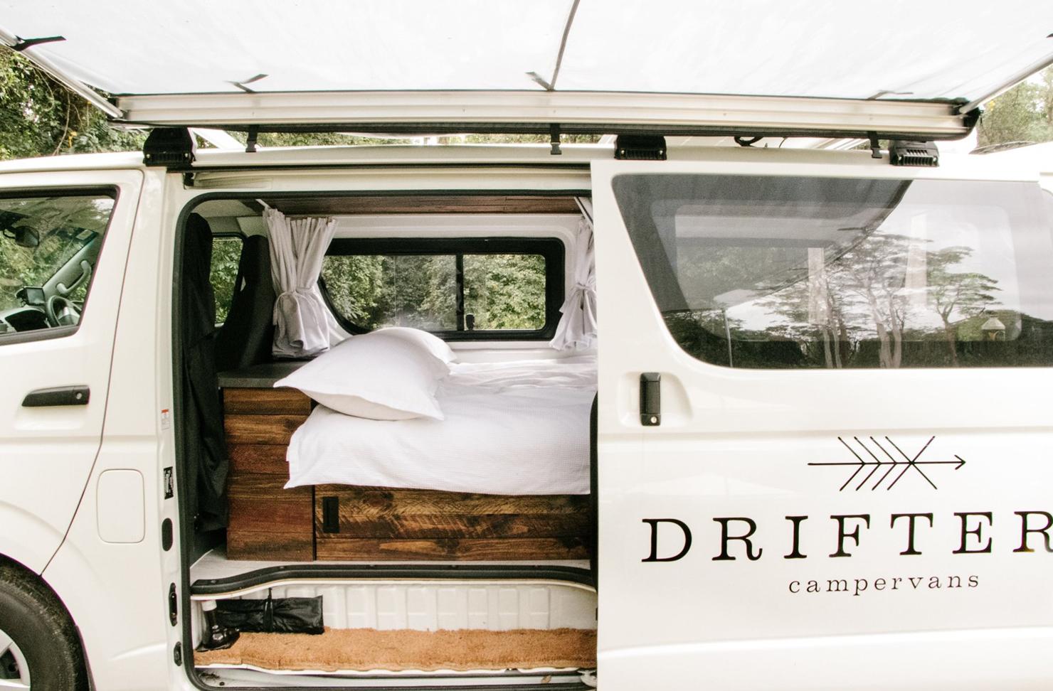 A white camper van with a mattress inside.