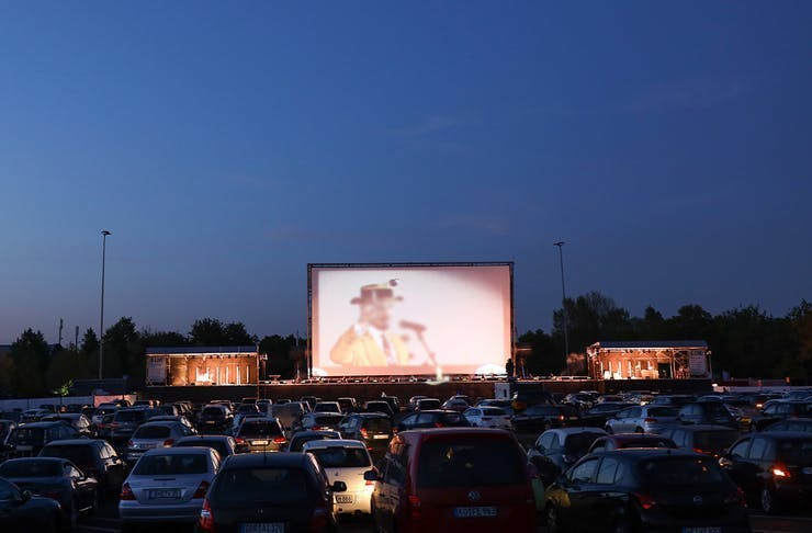 Rows of cars sit in front of a large outdoor movie screen at a drive-in cinema.