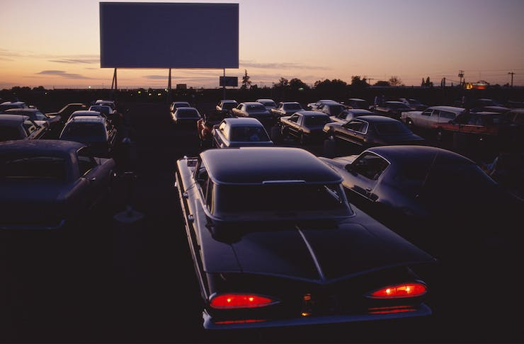 Retro cars parked in front of an outdoor movie screen