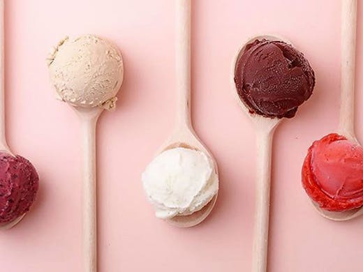 Four scoops of gelato, each sitting on a pink spoon in front of a pink background.