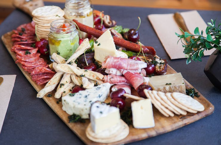 a cheese board piled with crackers, charcuterie and other foods