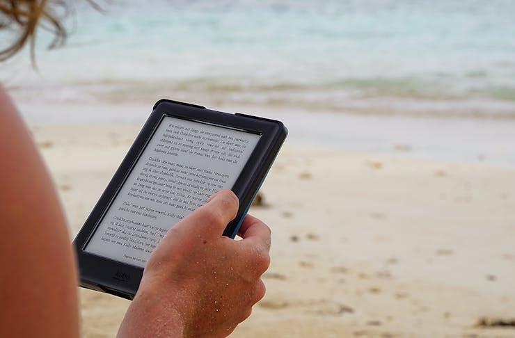 A woman reads an ebook on the beach