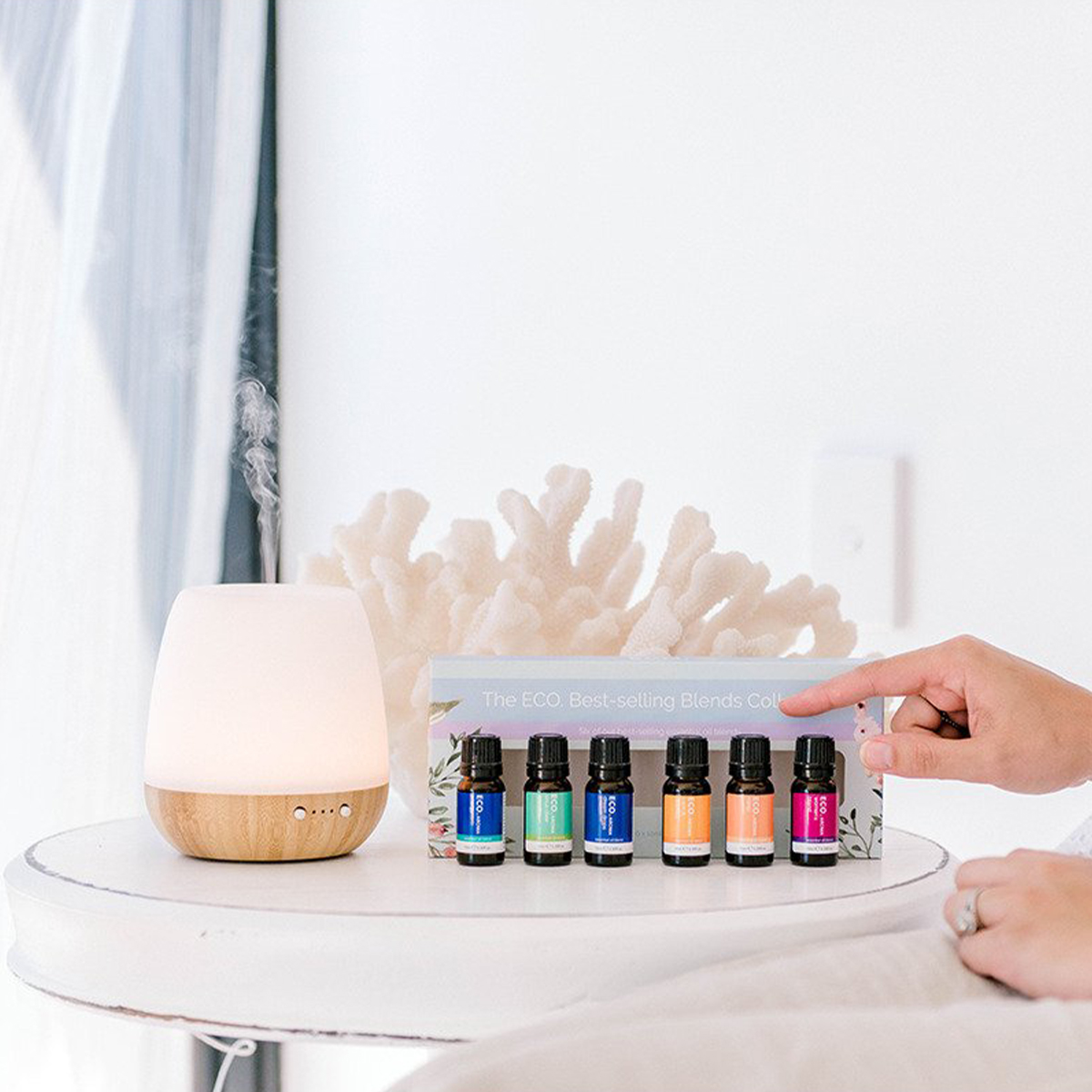 a white diffuser next to a row of essential oils