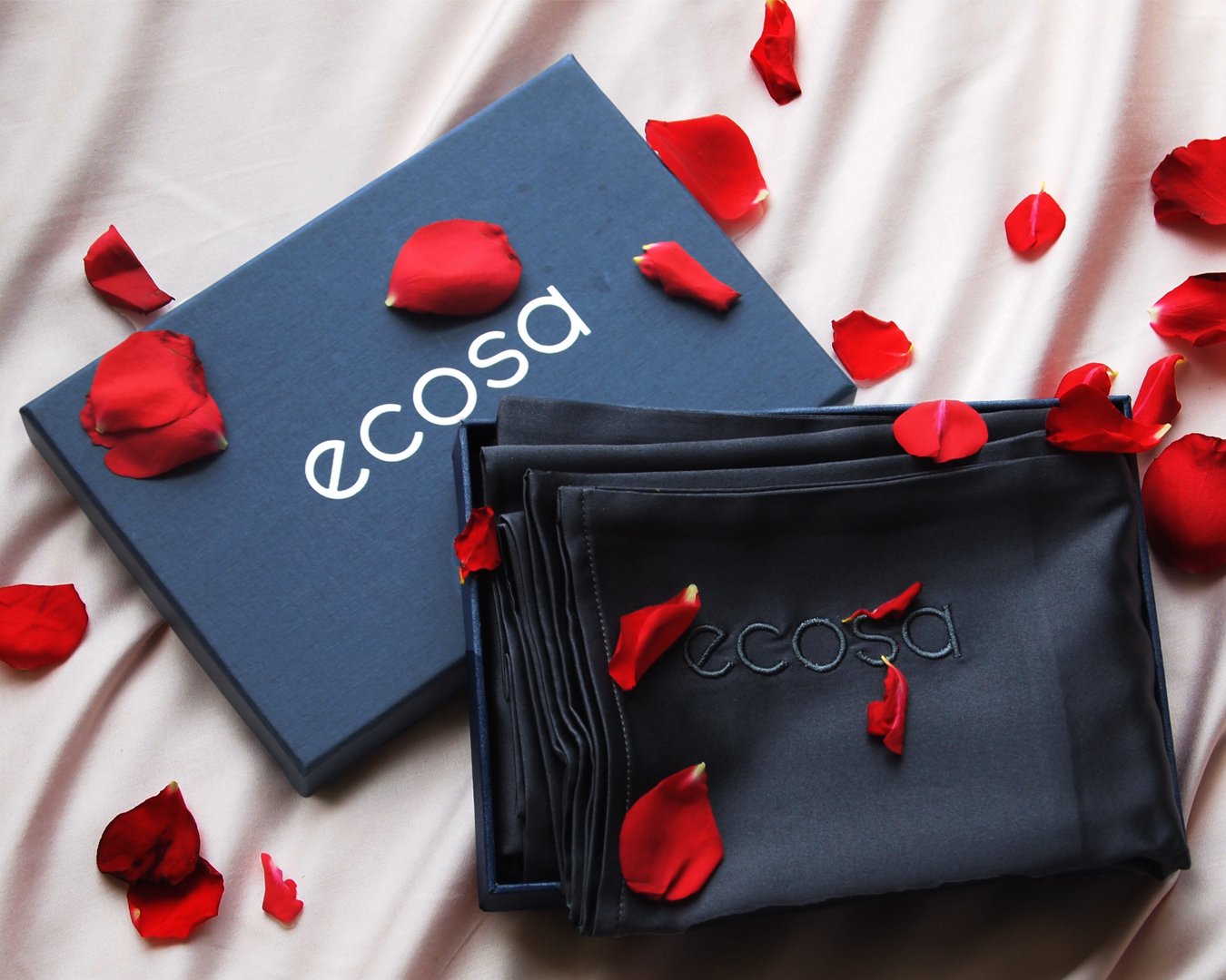 A black silk pillowcase from Acosa, covered in a scattering of rose petals