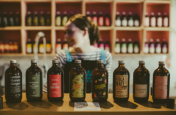 Girl standing in front of Six Barrel Soda co
