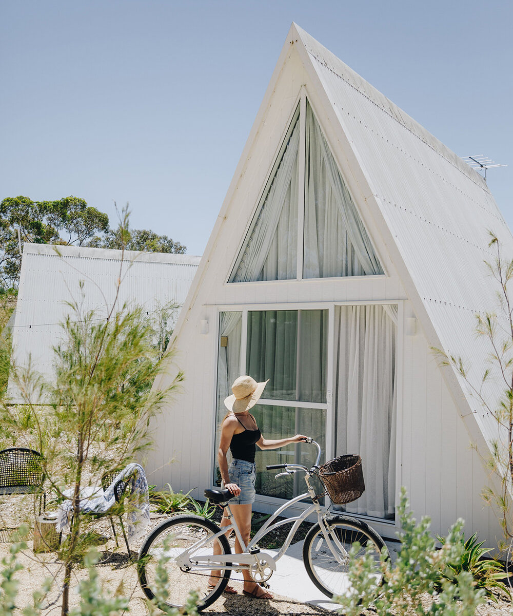 Woman stands with bike outside a frame chalet