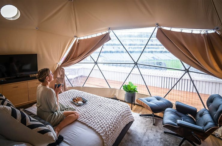 A girl sits on the bed in the Eden Park glamping accommodation looking pleased as punch with a cup of tea in her hands.
