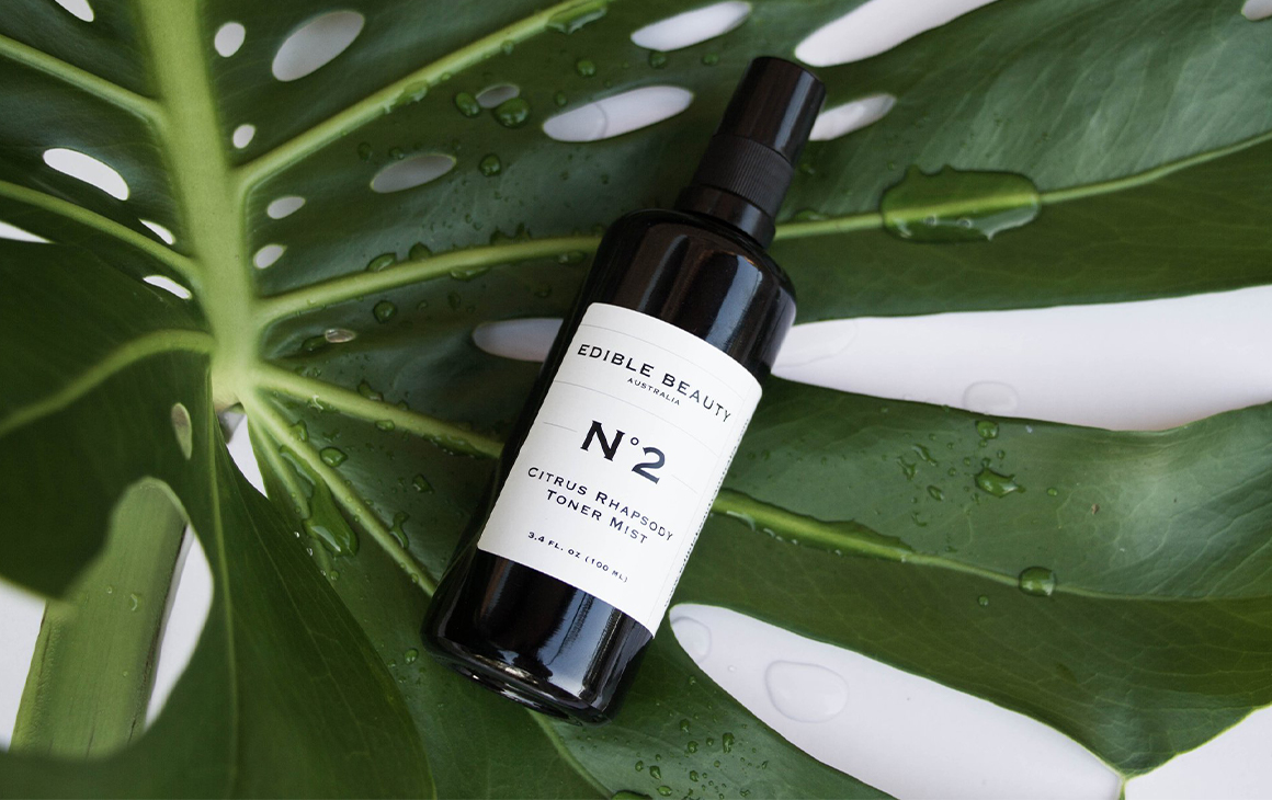 A bottle of Edible Beauty cleanser on a leaf.