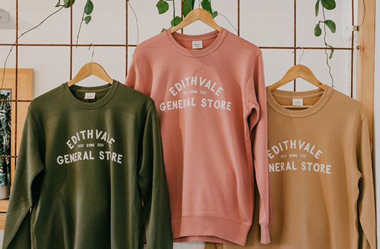 Three pastel-coloured sweaters all with the words
